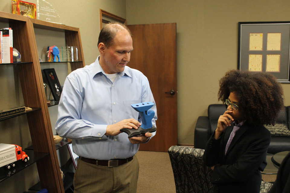 Photo - Kevin Hagan, president and CEO of Feed the Children, shows a pencil holder of the charity's logo to Joshua Williams, 12, who leads his own nonprofit organization, Joshua's Heart, that he started at age 5 after Feed the Children inspired him. The pencil holder was crafted through Feed the Children's carpentry program in Honduras. PHOTO PROVIDED.