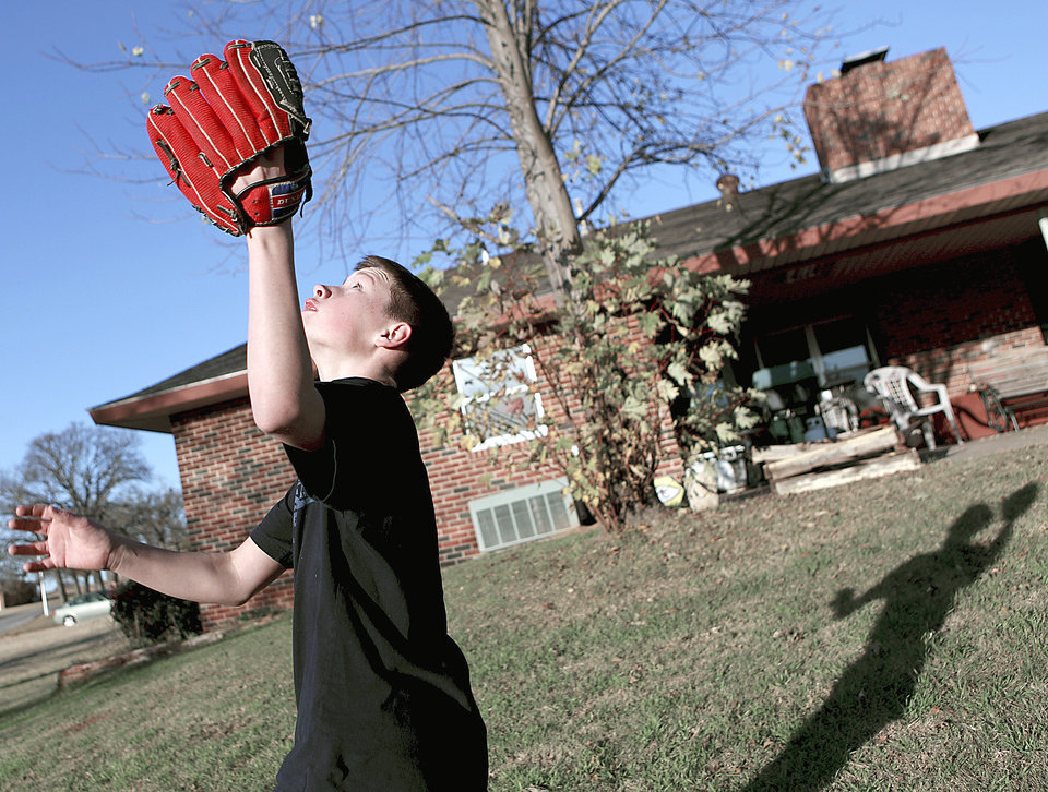 Chris, a resident at Boys Ranch Town in Edmond, plays catch in the yard outside one of the houses.  Photo By John Clanton, The Oklahoman