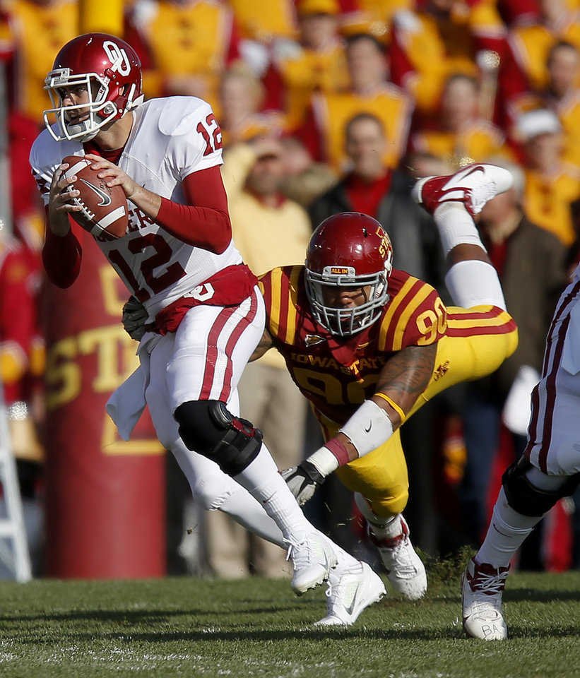 Photo - Oklahoma's Landry Jones (12) scrambles past Iowa State's Cleyon Laing (90) during a college football game between the University of Oklahoma (OU) and Iowa State University (ISU) at Jack Trice Stadium in Ames, Iowa, Saturday, Nov. 3, 2012. Oklahoma won 35-20. Photo by Bryan Terry, The Oklahoman
