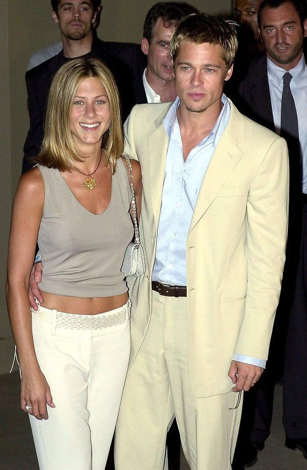 Photo - FILE - In this June 28, 2001 file photo, American actors Brad Pitt and his wife, Jennifer Aniston, arrive to attend Giorgio Armani Spring/Summer 2002 menswear collection presented in Milan, Italy. In contrast to Brangelina's smallish, tight-as-a-drum ceremony, Pitt's last wedding to Aniston was huge and over the top. The $1 million ceremony in 2000 included a 40-piece gospel choir, floating lotus flowers, a 13-minute fireworks display and imported candles from Thailand. (AP Photo/Luca Bruno, file)