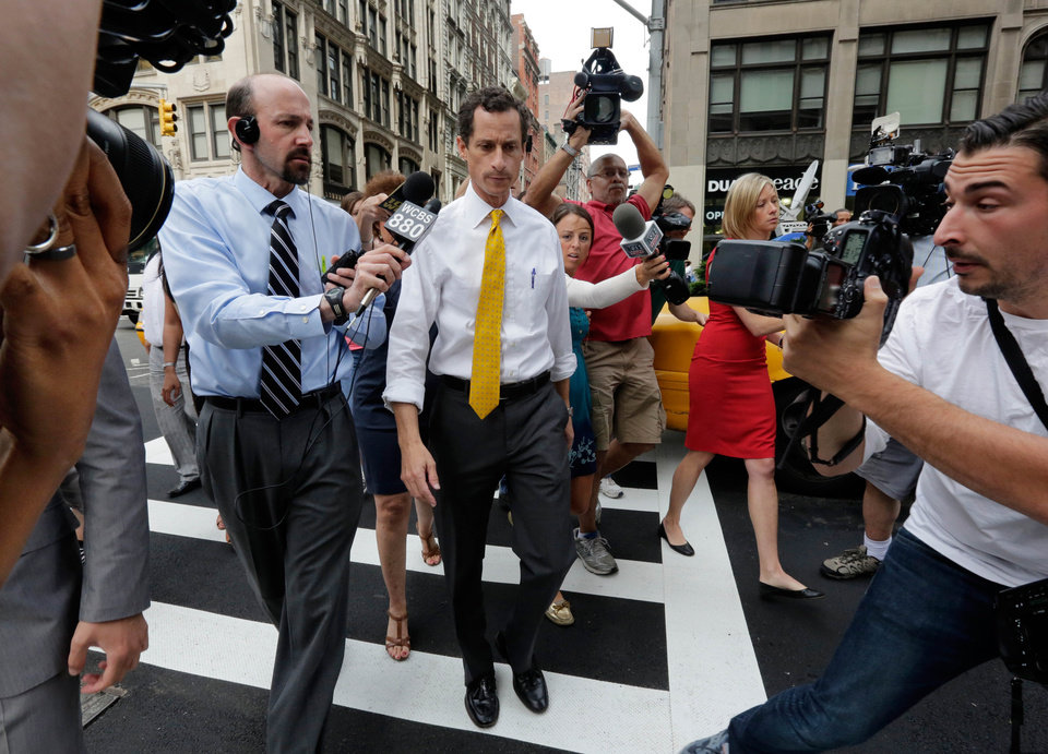Photo - New York City mayoral candidate Anthony Weiner is pursued by reporters after leaving his apartment in New York on Wednesday, July 24, 2013. The former congressman acknowledged sending explicit text messages to a woman as recently as last summer, more than a year after sexting revelations destroyed his congressional career. (AP Photo/Richard Drew)