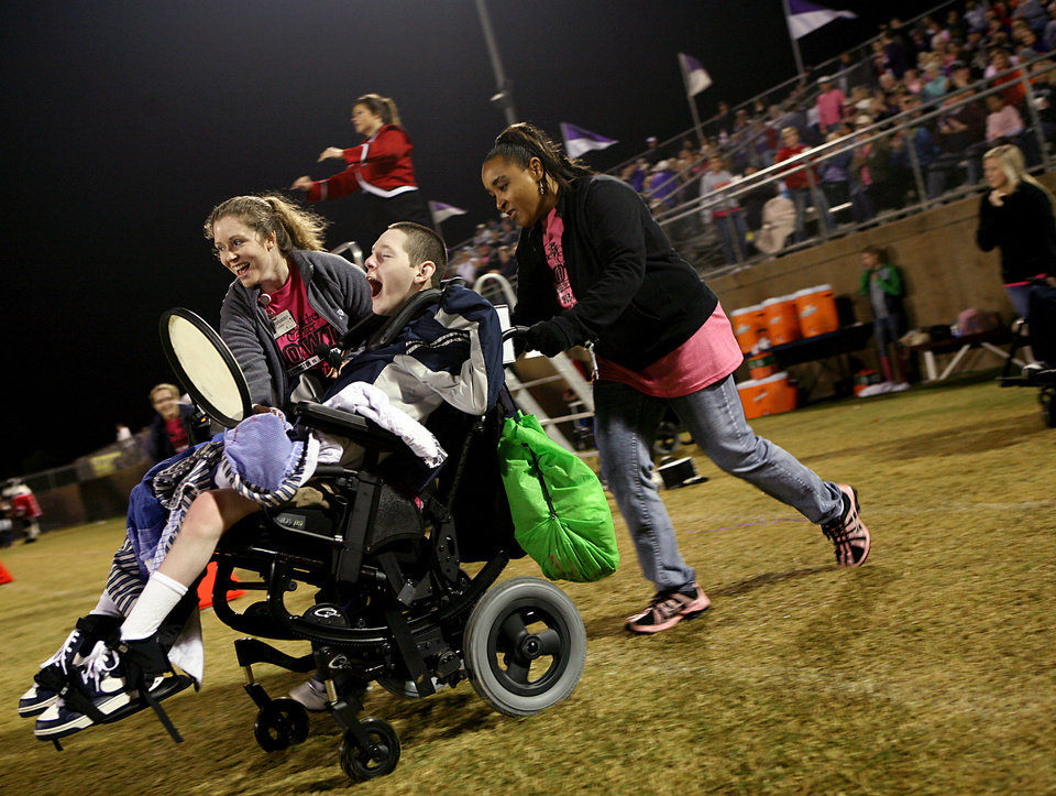 Photo - Chris Schatz reacts as he is pushed onto the field by nurse Sydney Stell, right, and music therapist Rachel Nowels at halftime of the  high school football game between Bethany and Washington in Bethany, Okla., on Friday, September 16, 2011. Residents of The Children's Center played drums with the high school bands from Washington and Bethany. Photo by John Clanton, The Oklahoman