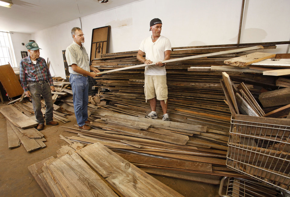 "From left, J. D. Crosby, Wayland Bishop,  and Dan Riedemann among the old boards  that will be used to reconstruct the   Woody Guthrie ""London House. "" The lumber is stacked in a back room at the Okemah Historical Society Museum on W. Broadway in downtown Okemah.   The Duke family and 19th Century Restorations are raising funds  to reconstruct Woody Guthrie's birth home in Okemah.  Bishop is a board member for the Okemah Historical Society and he helped transport the wood to the museum. Riedemann is supervising the reconstruction of Guthrie's home.  Crosby is a volunteer tour guide at the museum.     Photo taken June 7,  2012.    Photo by Jim Beckel, The Oklahoman"