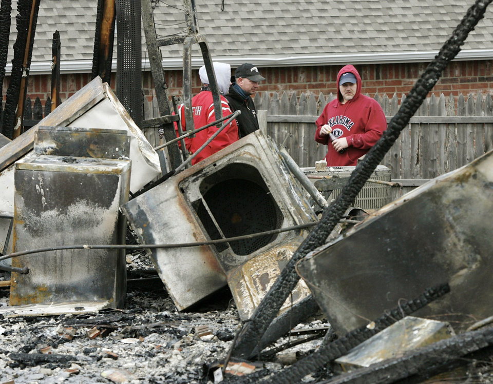 Photo - David Dolney, far right, and relatives look at damage to the home where he and his wife, Niki, lived in Oakwood East Royale neighborhood, 11365 Queensland Ct.  The house was one of numerous structures destroyed in Thursday's wildfires.   Photo by JIM BECKEL, THE OKLAHOMAN ORG XMIT: KOD