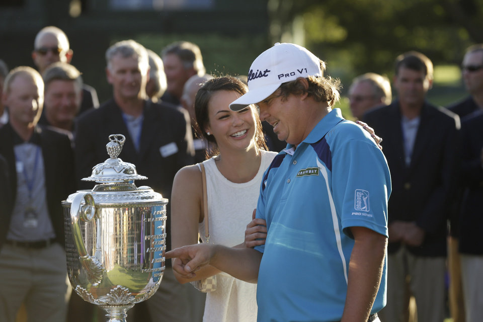 Photo - Jason Dufner, right, looks at the Wanamaker Trophy, with is wife Amanda after winning on the PGA Championship golf tournament at Oak Hill Country Club, Sunday, Aug. 11, 2013, in Pittsford, N.Y. (AP Photo/Charlie Neibergall)