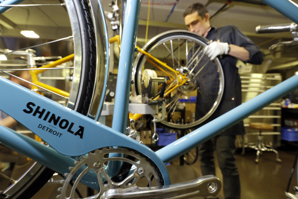 Photo - In a photo from April 10, 2013 in Detroit Alex Stchekine assembles a Shinola bicycle at the company's manufacturing facility. Detroit has a long history of making stuff _ cars, steel, even popcorn and is now home to a facility devoted to the production of wristwatches and bicycles. The frames are produced in Wisconsin and assembled in Detroit. (AP Photo/Carlos Osorio)