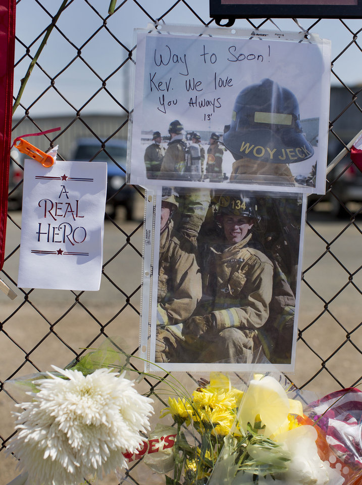 Photo - A photo of Hotshot firefighter Kevin Woyjeck hangs on a fence outside the Granite Mountain Interagency Hotshot Crew fire station, Tuesday, July 2, 2013 in Prescott, Ariz. Woyjeck was one of 19 members of the Granite Mountain Hotshots, based in Prescott, who were killed Sunday when a windblown wildfire overcame them north of Phoenix. It was the deadliest single day for U.S. firefighters since 9/11. Fourteen of the victims were in their 20s.   (AP Photo/Julie Jacobson)