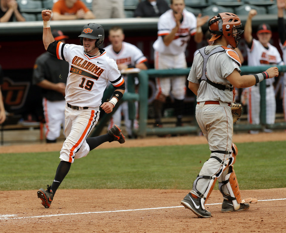 Photo - OSU's Aaron Cornell (19) runs past UT catcher Tres Barrera (1) to score the tying run in the eighth inning during a college baseball game between Texas and Oklahoma State in the Big 12 baseball tournament at the Chickasaw Bricktown Ballpark in Oklahoma City,  Saturday, May 24, 2014. OSU won 3-1 to force an elimination game. Photo by Nate Billings, The Oklahoman