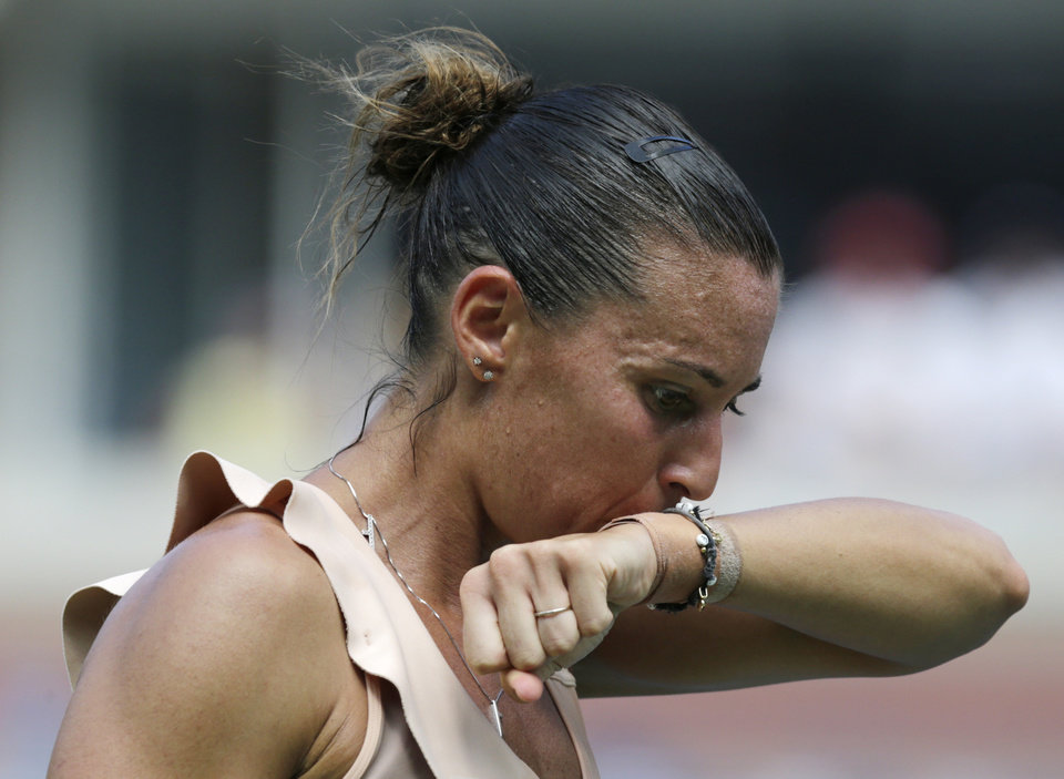 Photo - Flavia Pennetta, of Italy, wipes sweat from her face between serves against Casey Dellacqua, of Australia, during the fourth round of the 2014 U.S. Open tennis tournament, Monday, Sept. 1, 2014, in New York. (AP Photo/Charles Krupa)