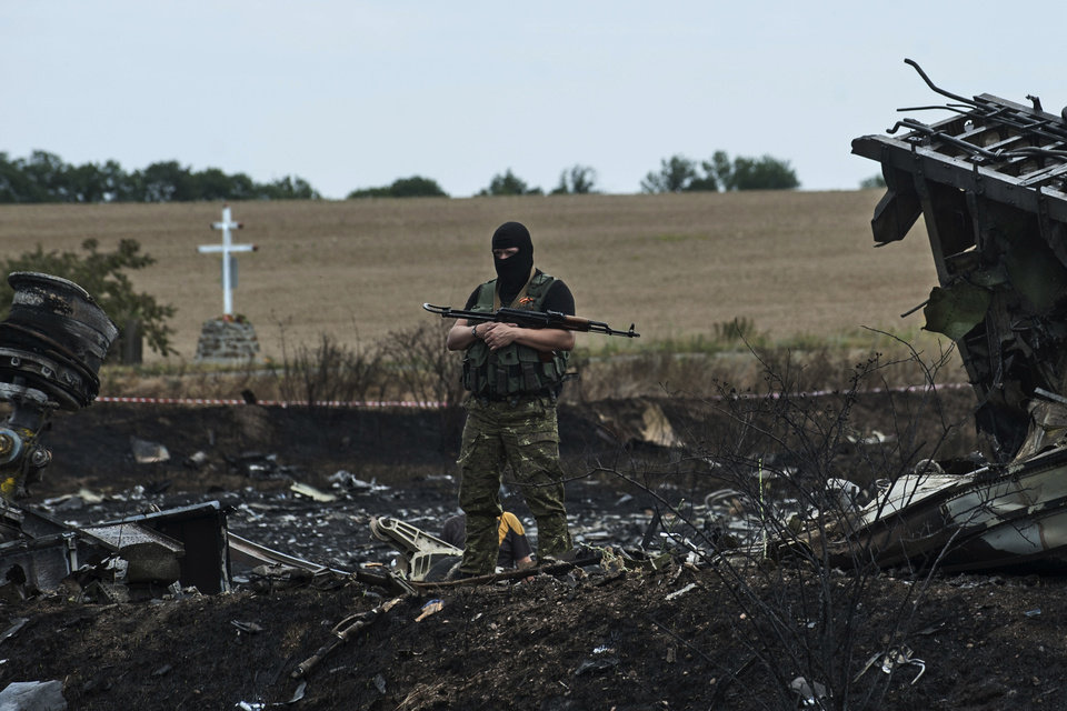 Photo - A pro-Russian fighter guards the crash site of Malaysia Airlines Flight 17 near the village of Hrabove, eastern Ukraine, Sunday, July 20, 2014. Rebels in eastern Ukraine took control Sunday of the bodies recovered from downed Malaysia Airlines Flight 17, and the U.S. and European leaders demanded that Russian President Vladimir Putin make sure rebels give international investigators full access to the crash site.(AP Photo/Evgeniy Maloletka)