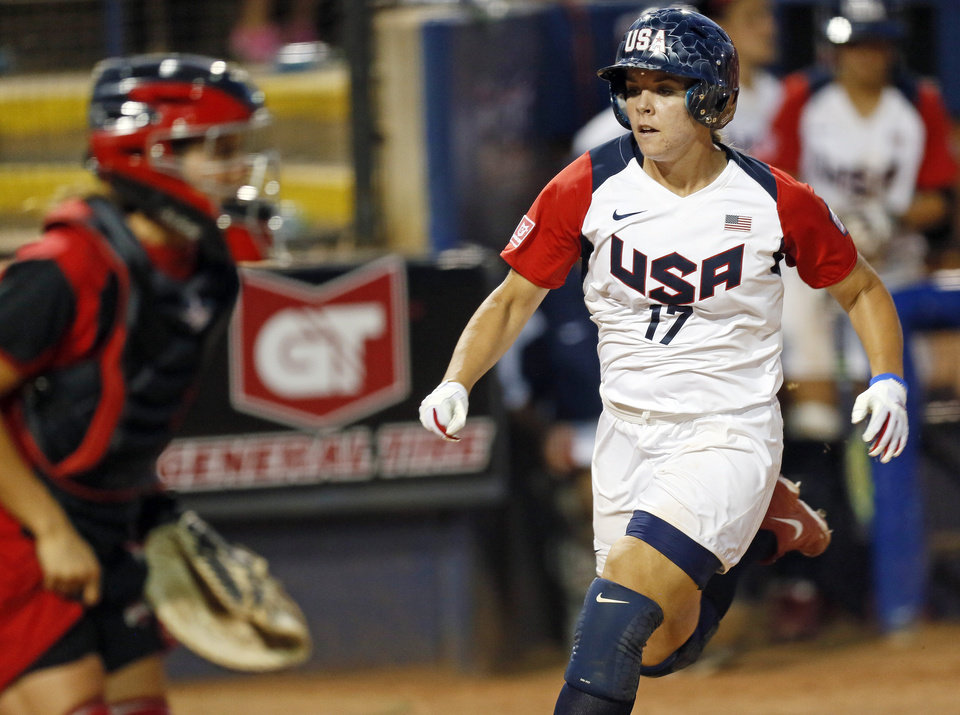 Photo - Lindsey Ziegenhirt (17) of the United States runs home to score near Natalie Wideman (20) of Canada in the sixth inning during a game between Team USA and Canada in the World Cup of Softball at ASA Hall of Fame Stadium in Oklahoma City, Thursday, July 11, 2013. Team USA won 7-0 in 6 innings. Photo by Nate Billings, The Oklahoman