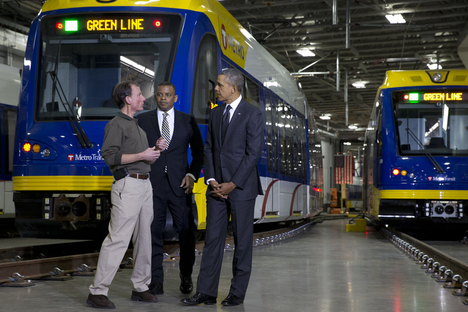 Photo - Mark Fuhrmann, New Start Program Director of Metro Transit, left, talks with President Barack Obama and Transportation Secretary Anthony Foxx, during a tour of the Metro Transit Light Rail Operations and Maintenance Facility in St. Paul, Minn., Wednesday, Feb. 26, 2014. In Minnesota Obama is expected to speak at Union Depot rail and bus station with a proposal asking Congress for $300 billion to update the nation's roads and railways, and about a competition to encourage investments to create jobs and restore infrastructure as part of the President's Year of Action. (AP Photo/Jacquelyn Martin)