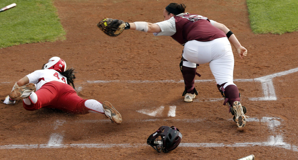 Sooner Lauren Chamberlain slides home safe under the tag of Meagan May in NCAA Super Regional softball as the University of Oklahoma (OU) Sooners defeats Texas A&M 10-2 at Marita Hines Field on Friday, May 24, 2013 in Norman, Okla. Photo by Steve Sisney, The Oklahoman