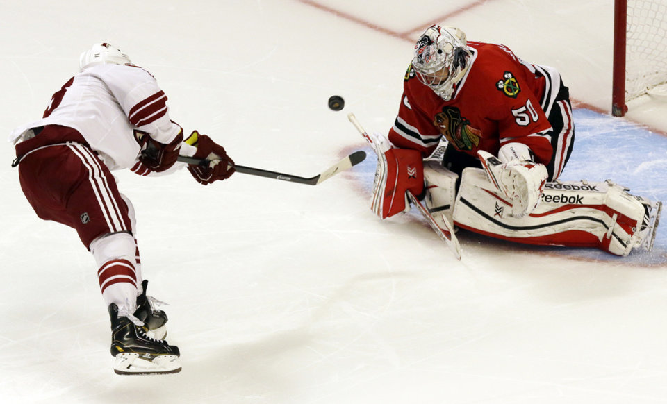 Photo - Chicago Blackhawks goalie Corey Crawford, right, blocks a shot by Phoenix Coyotes' Mike Ribeiro in a shootout during an NHL hockey game in Chicago, Thursday, Nov. 14, 2013. The Blackhawks won 5-4. (AP Photo/Nam Y. Huh)