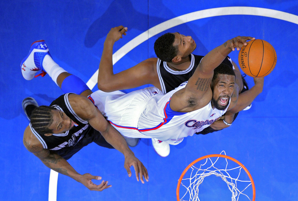 Photo -   Los Angeles Clippers center DeAndre Jordan, right, grabs a rebound away from San Antonio Spurs forward Kawhi Leonard, left, and forward Boris Diaw of France during the first half in Game 4 of an NBA basketball playoffs Western Conference semifinal, Sunday, May 20, 2012, in Los Angeles. (AP Photo/Mark J. Terrill)