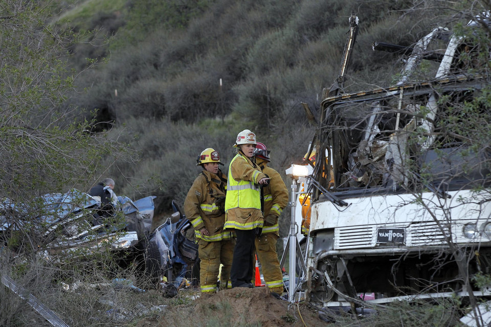 Photo - San Bernardino  Investigators examine wreckage Monday Feb. 4, 2012, after a tour bus accident in the Southern California mountains near San Bernardino.  The accident Sunday killed at least 8 people.  ( AP Photo/Nick Ut)