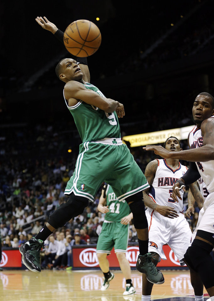 Photo - Boston Celtics' Rajon Rondo, left, loses control of the ball while going up for a shot against Atlanta Hawks' Paul Millsap, right, in the fourth quarter of an NBA basketball game, Wednesday, April 9, 2014, in Atlanta. The Hawks won 105-97. (AP Photo/David Goldman)