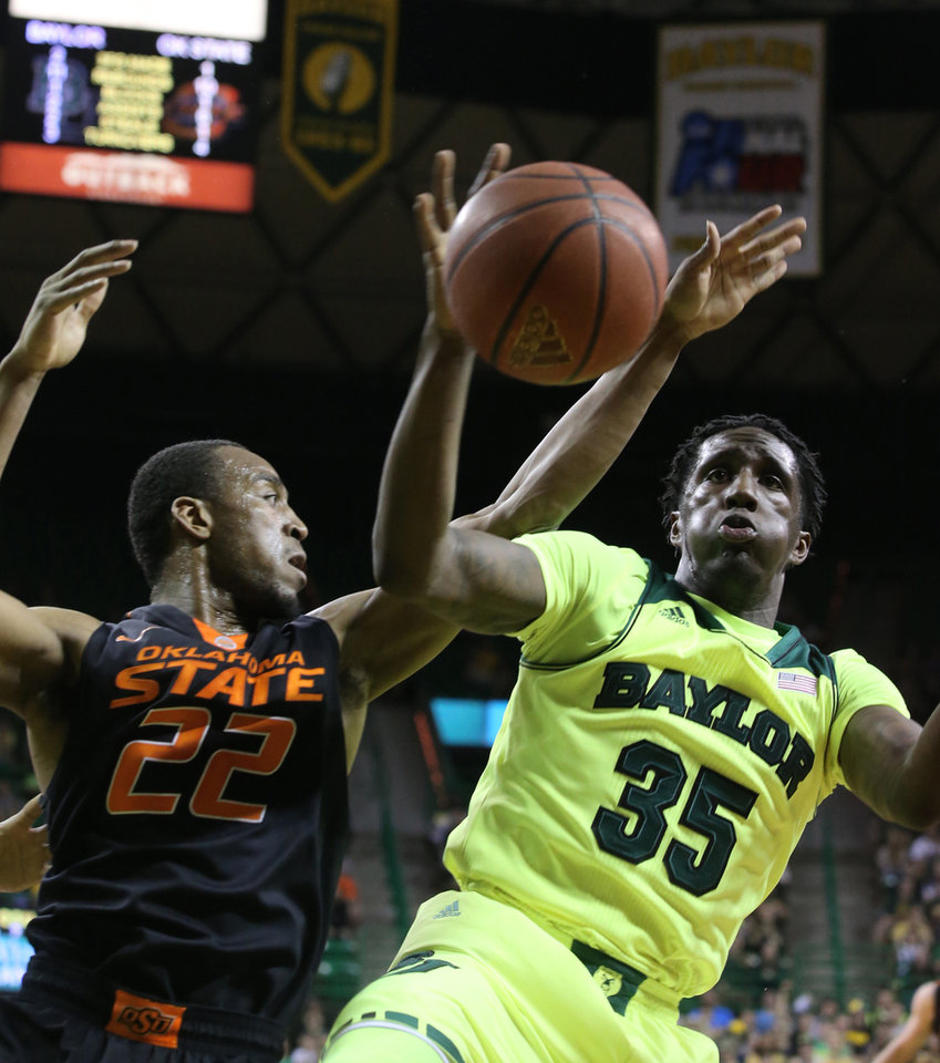 Photo - Baylor forward Taurean Prince (35), right,  reaches for a loose rebound with Oklahoma State guard Markel Brown (22), left, in the first half of an NCAA college basketball game, Monday, Feb. 17, 2014, in Waco, Texas. (AP Photo/Waco Tribune Herald, Rod Aydelotte)
