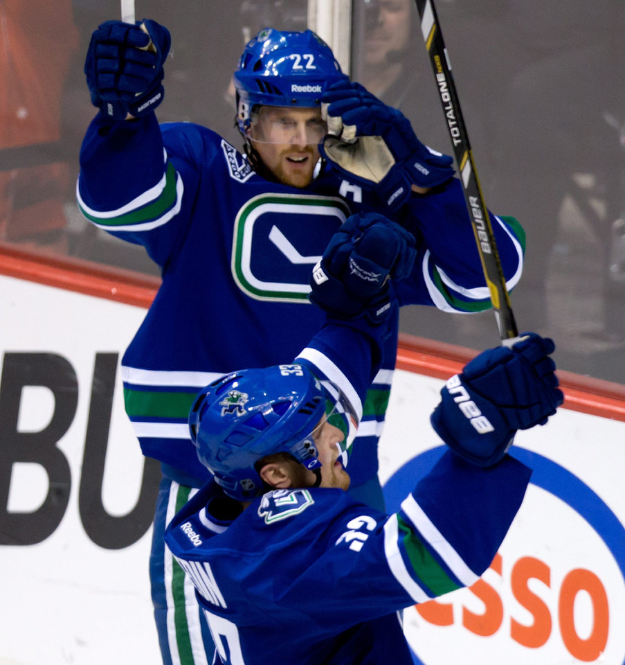Photo - Vancouver Canucks' Henrik Sedin, bottom, of Sweden, celebrates his goal against the San Jose Sharks with his twin brother Daniel Sedin, of Sweden, during the second period of an NHL hockey game in Vancouver, British Columbia, Tuesday, March 5, 2013. (AP Photo/The Canadian Press, Darryl Dyck)