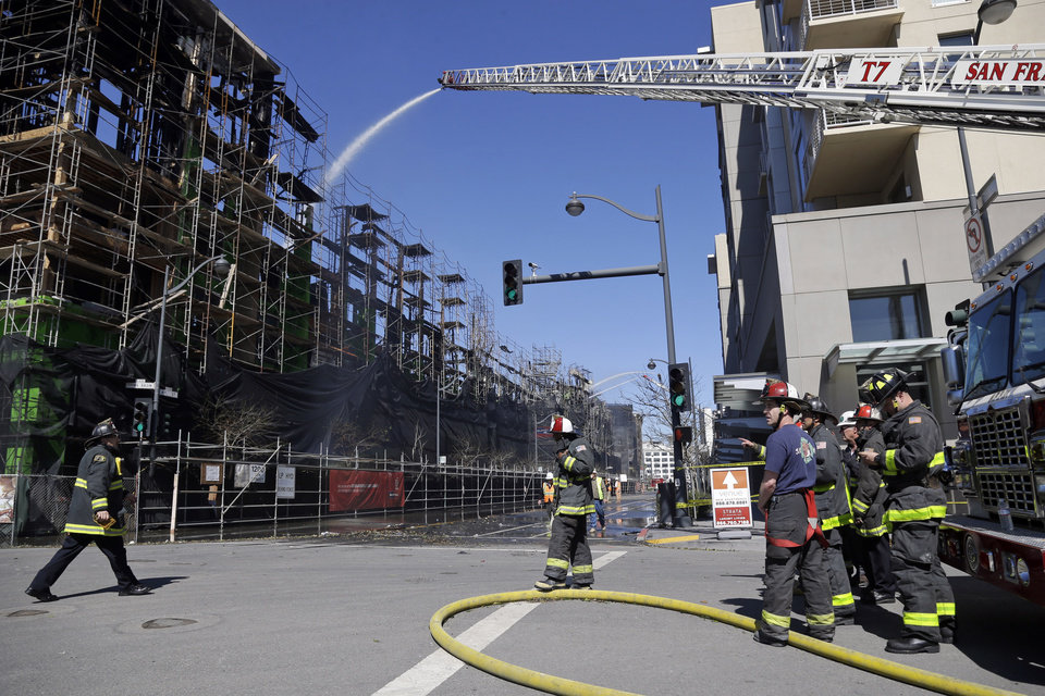 Photo - Firefighters continue to work a day after a structure fire in the Mission Bay neighborhood on Wednesday, March 12, 2014, in San Francisco. Hundreds of Mission Bay apartment dwellers chased from their homes by a huge fire at a building under construction are fortunate to have homes to return to, San Francisco Mayor Ed Lee said Wednesday, as firefighters put out hot spots and sought to determine the cause of the blaze. AP Photo/Marcio Jose Sanchez)