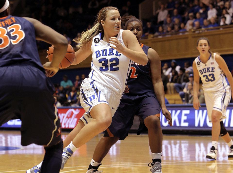 Photo - Duke's Tricia Liston (32), who scored a game-high 21 points, drives to the basket between Virginia's Raeshaun Gffney, left, and Breyana Mason, center, during the first half of an NCAA women's college basketball game, Thursday, Jan. 16, 2014, in Durham, N.C. Duke won 90-55. (AP Photo/Ted Richardson)