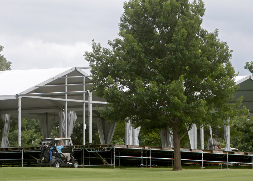 Photo - Golfers drive by temporary buildings that have been erected on the course at Oak Tree National Country Club in preparation for the 2014 U.S. Senior Open, held in July, on June 12, 2014. Photo by KT King/The Oklahoman