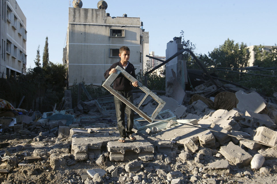 A Palestinian boy holds a window pane taken from a damaged house hit in an Israeli strike, in Gaza City, Thursday, Nov. 15, 2012. Israeli aircraft, tanks and naval gunboats pounded the Hamas-ruled Gaza Strip and rocket salvoes thudded into southern Israel, as residents on both sides of the frontier holed up at home in anticipation of heavy fighting on the second day of Israel\'s offensive against Islamic militants. (AP Photo/Hatem Moussa)