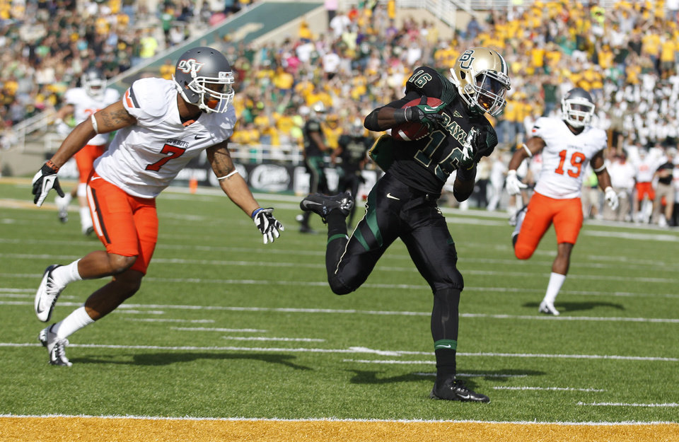 Photo - Baylor wide receiver Tevin Reese (16) runs in a touchdown pass against Oklahoma State safety Shamiel Gary (7) and cornerback Brodrick Brown (19) during the first half of an NCAA college football game Saturday, Dec. 1, 2012, in Waco, Texas. (AP Photo/LM Otero)