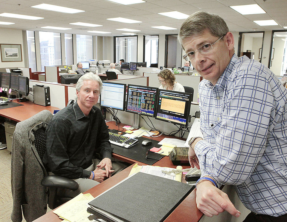 Photo - Gary Tillman, vice president of institutional investments for BOSC Inc., and Hal Brown, BOSC senior vice president, staff the firm's Oklahoma City trading room Monday.