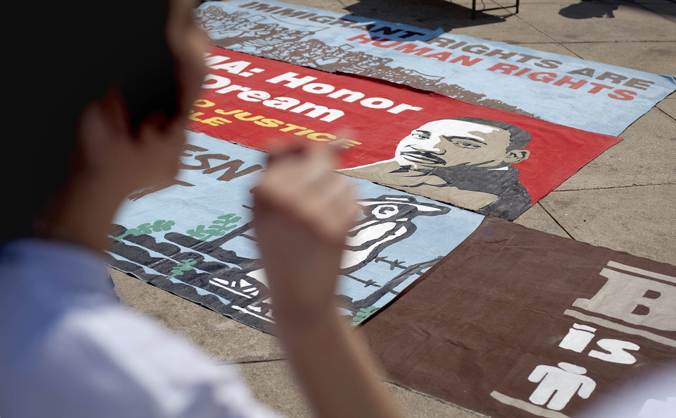 """Photo -   An image of the Rev. Martin Luther King Jr. is seen on a banner spread out in front of the Georgia Capitol for a May Day immigration rally Tuesday, May 1, 2012, in Atlanta. The May Day rally at the Capitol Tuesday that organizers called a """"historic coming together"""" of immigrants and working people was significantly smaller than in recent years, drawing only about 100 people. (AP Photo/David Goldman)"""