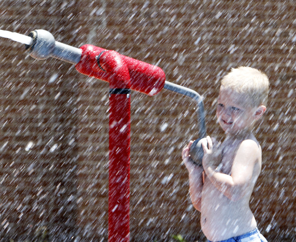 Photo - Wild art. Nicholas Thorn, 3, shoots a water cannon in a splash par at Macklanburg Park, 117 and north McKinley, Monday, June 25, 2012. Photo By David McDaniel/The Oklahoman