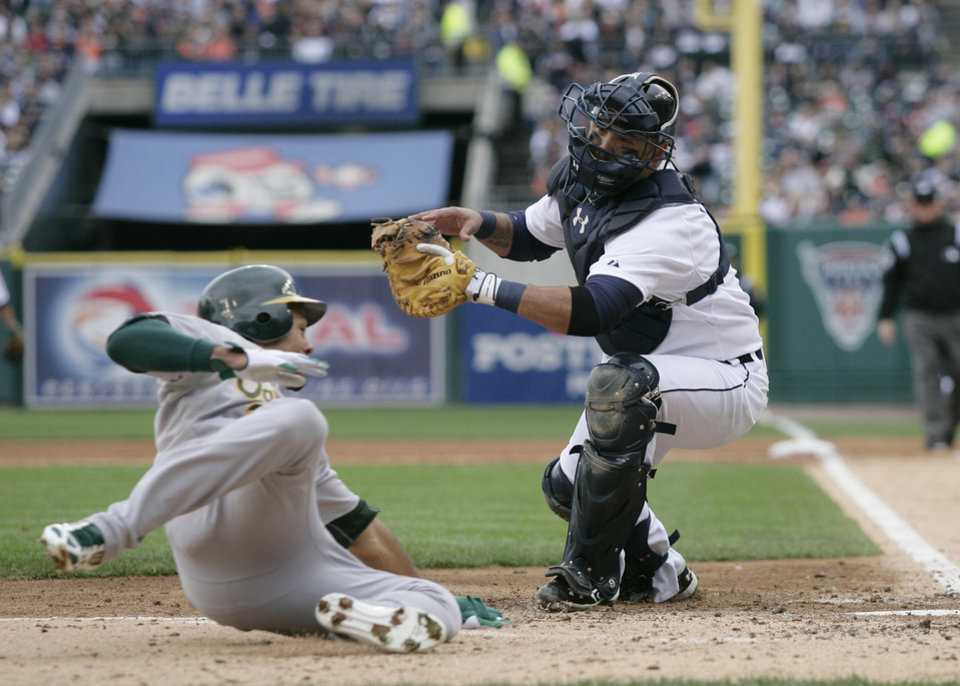 Oakland Athletics' Coco Crisp is tagged out by Detroit Tigers catcher Gerald Laird (9) trying to score from second on teammate Brandon Moss' single to right during the third inning of Game 2 of the American League division baseball series, Sunday, Oct. 7, 2012, in Detroit. (AP Photo/Duane Burleson)