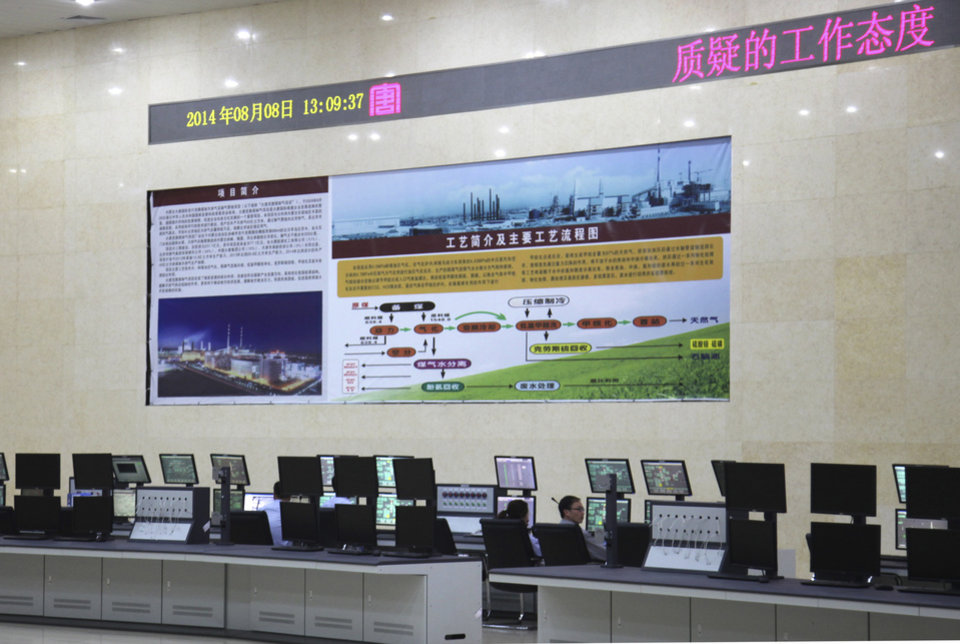 Photo - In this Friday, Aug. 8, 2014 photo, workers monitor screens at a control center for a state-of-the-art power plant that turns millions of tons of coal every year into methane in northern China's Inner Mongolia province. This is the first of more than 60 coal-to-gas plants China wants to build, mostly in remote parts of the country where ethnic minorities have farmed and herded for centuries. Fired up in December, the multi-billion dollar plant bombards millions of tons of coal with water and heat to produce methane, which is piped to Beijing to generate electricity. (AP Photo/Jack Chang)