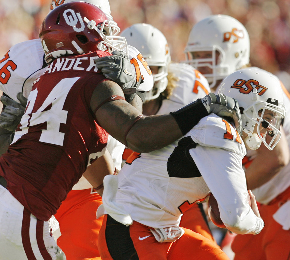 Photo - OU's Frank Alexander (84) sacks OSU quarterback Zac Robinson (11) in the fourth quarter of the Bedlam college football game between the University of Oklahoma Sooners (OU) and the Oklahoma State University Cowboys (OSU) at the Gaylord Family-Oklahoma Memorial Stadium on Saturday, Nov. 28, 2009, in Norman, Okla. OU won, 27-0.