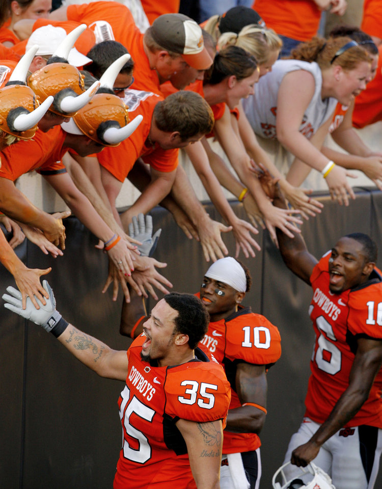 Photo - OSU players Marcus Brown (35) Tommy Devereaux (10) and Perrish Cox celebrate with fans following the college football game between the Oklahoma State University Cowboys (OSU) and the Texas Tech University Red Raiders (TTU) at Boone Pickens Stadium  on Saturday, Sept. 22, 2007, in Stillwater, Okla. 