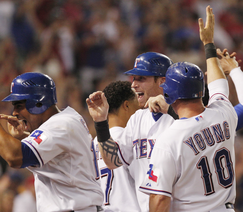 Texas Rangers Nelson Cruz, left, Josh Hamilton and Michael Young celebrate after they scored on a three-run triple by Craig Gentry in the eighth inning of a baseball game against the Oakland Athletics, Friday, June 29, 2012, in Arlington, Texas. The Rangers won the game 4-3. (AP Photo/Tim Sharp)