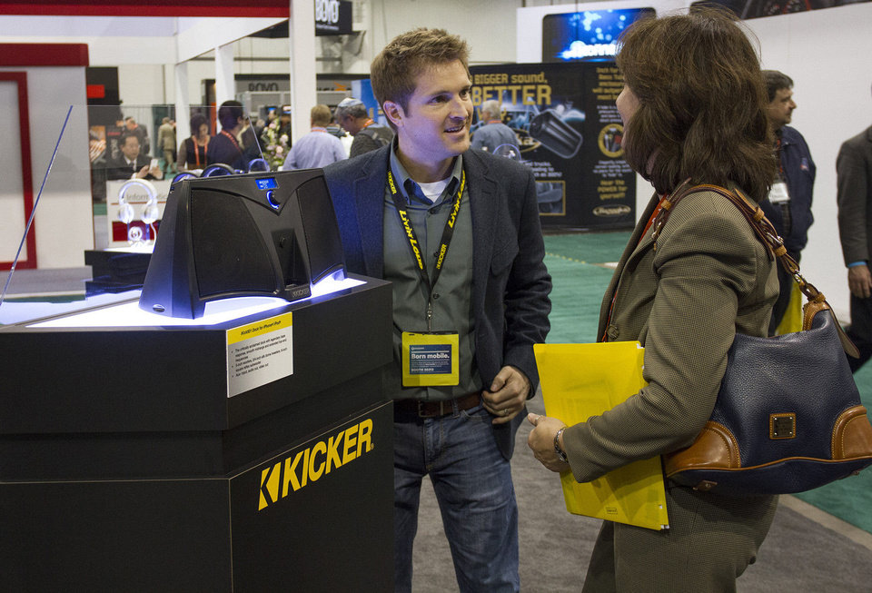 Jeremy Bale, left, talks to a buyer Wednesday at Kicker's home and personal products booth at the 2013 International CES consumer electronics show in Las Vegas. <strong> - PAUL RIEDL</strong>