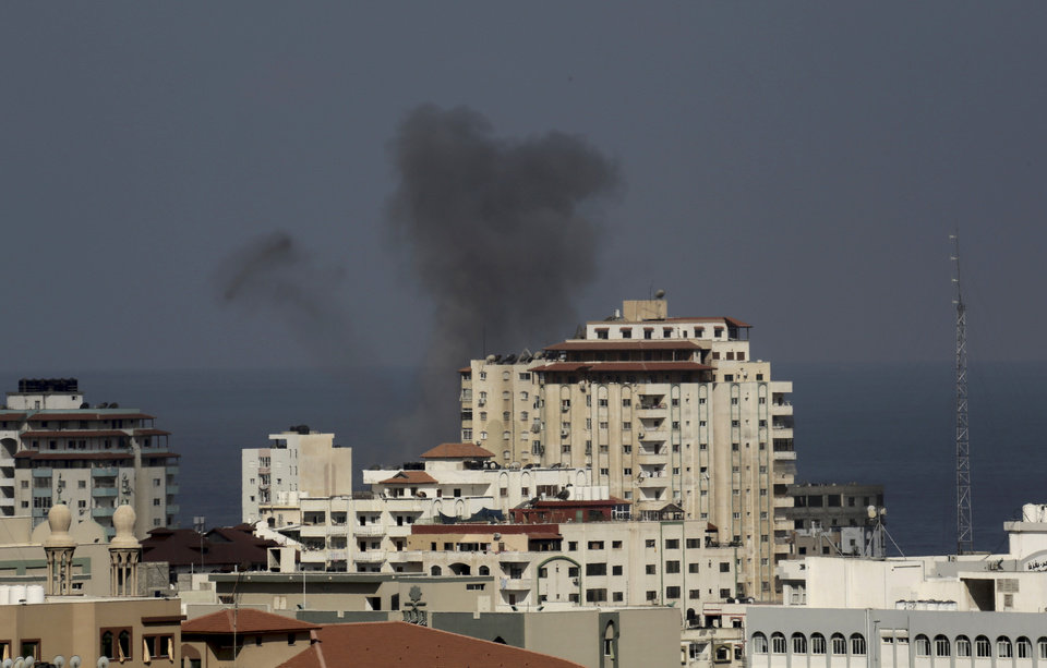 Photo - Smoke rises after an Israeli missile strike in Gaza City, in the northern Gaza Strip, Wednesday, July 16, 2014. Israel on Wednesday intensified air attacks on Hamas targets in the Gaza Strip following a failed Egyptian cease-fire effort, targeting the homes of four senior leaders of the Islamic militant movement and ordering tens of thousands of residents to evacuate border areas.(AP Photo/Adel Hana)