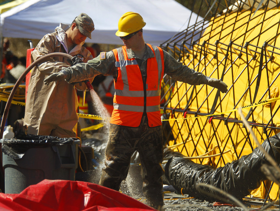 Photo - Workers go through the first stage of the decontamination process after coming off the site of a fatal mudslide near Oso, Wash., on Tuesday, April 1, 2014. The March 22 mudslide destroyed a  rural mountainside community northeast of Seattle. (AP Photo/The Herald, Mark Mulligan) MANDATORY CREDIT.