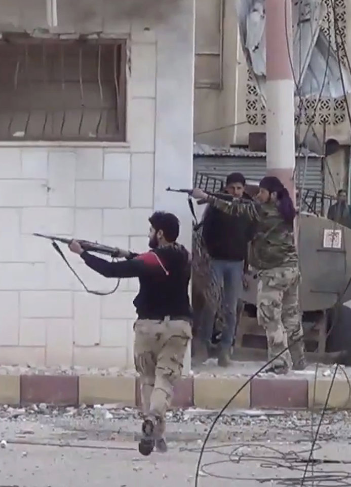 Photo - In this image taken from video obtained from the Shaam News Network, which has been authenticated based on its contents and other AP reporting, Free Syrian Army figthers fire at Syrian army soldiers during a fierce firefight in Daraa al-Balad, Syria, Monday March 18, 2013. Two years after the anti-Assad uprising began, the conflict has become a civil war, with hundreds of rebel group fighting Assad's forces across Syria and millions of people pushed from their homes by the violence. The U.N. says more than 70,000 people have been killed. (AP Photo/Shaam News Network via AP video)