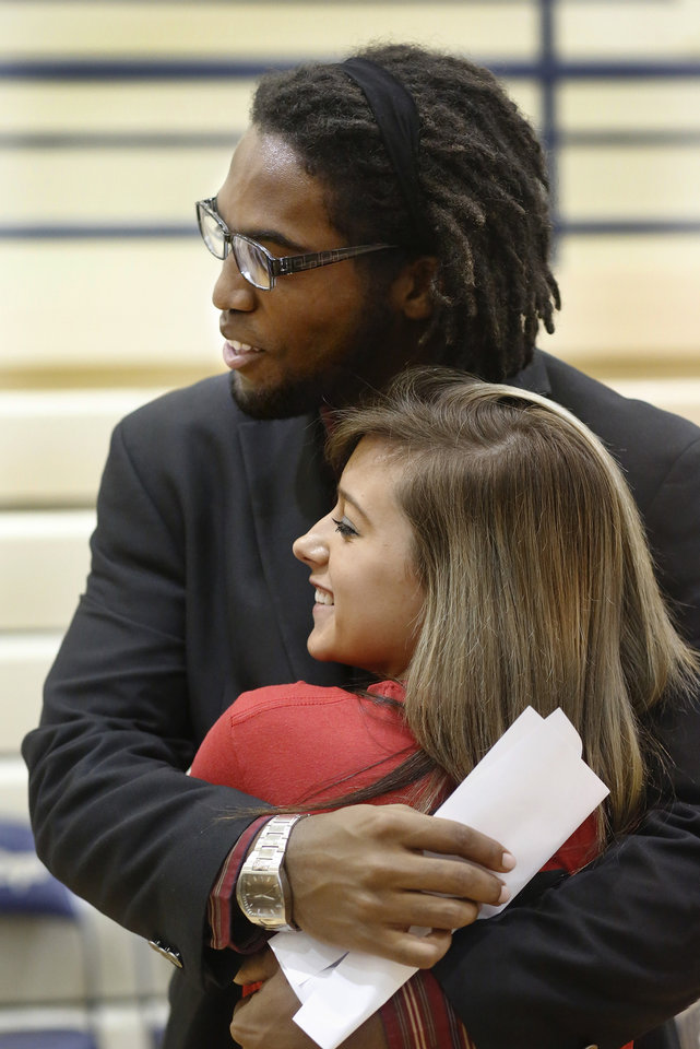 D. J. Ward, gets a hug from fellow senior Taylor Moore when he poses with her for a photo after he signed a letter of intent to play football at the University of Oklahoma. More than a dozen Southmoore High School athletes signed letters of intent to play at various colleges and universities during an afternoon signing ceremony in the school\'s gymnasium on Wednesday, Feb. 6, 2013. Photo by Jim Beckel, The Oklahoman