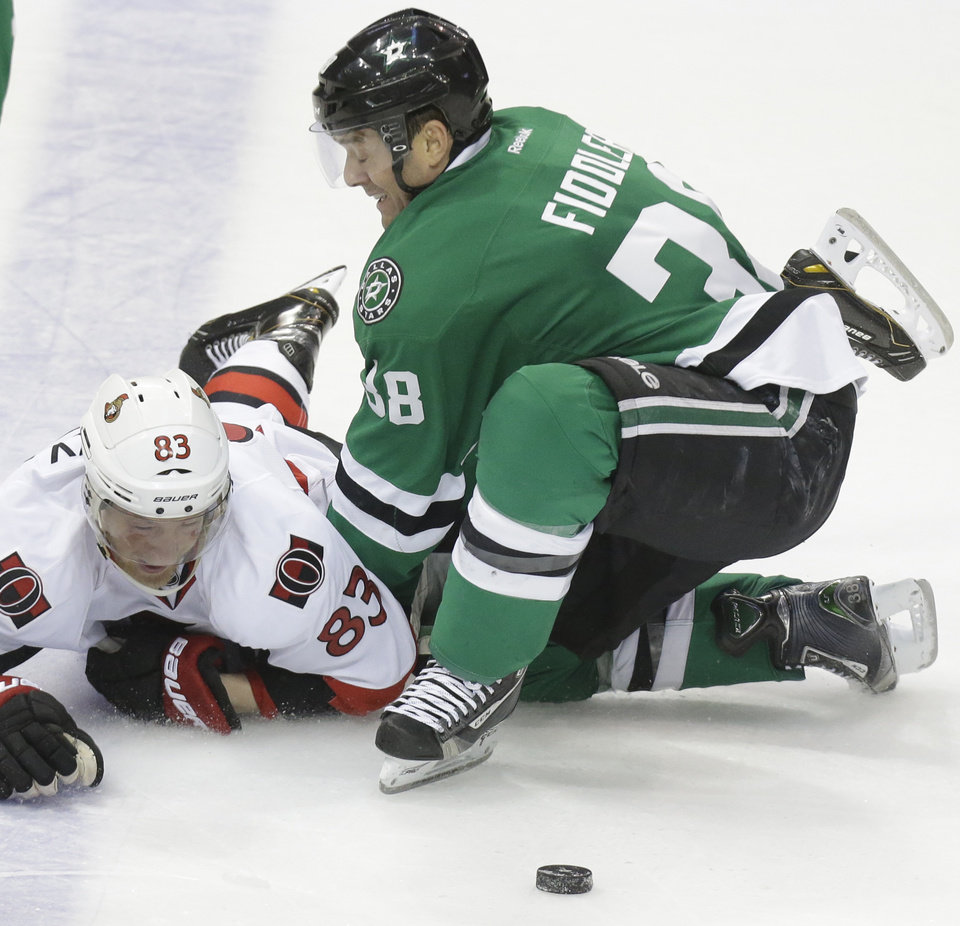Photo - Dallas Stars center Vernon Fiddler (38) knocks Ottawa Senators right wing Ales Hemsky (83) to the ice keeping him from the puck during the second period an NHL Hockey game, Saturday, March 22, 2014, in Dallas. (AP Photo/LM Otero)