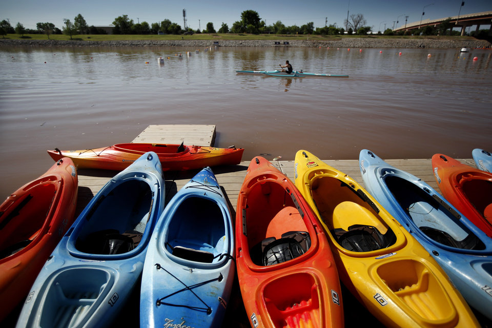 A competitors paddles pass boats lend up on the shore line during races for the USA Canoe/Kayak World Cup Team Trials on the Oklahoma River,  Saturday, April 21, 2012. Photo by Sarah Phipps, The Oklahoma