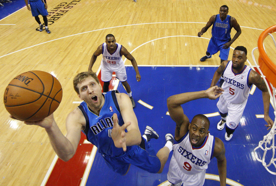 Photo - Dallas Mavericks' Dirk Nowitzki, left, of Germany, shoots as Philadelphia 76ers' James Anderson, right, defends during the first half of an NBA basketball game, Friday, Feb. 21, 2014, in Philadelphia. (AP Photo/Chris Szagola)