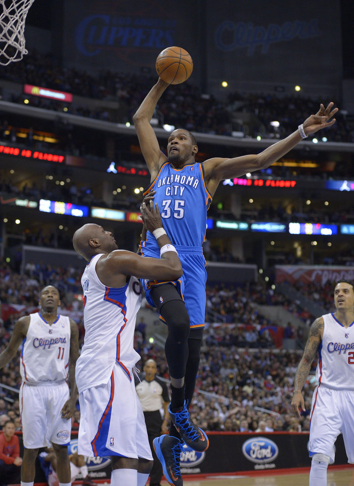 Photo - Oklahoma City Thunder forward Kevin Durant goes up for a dunk as Los Angeles Clippers forward Lamar Odom, second from left, defends while guard Jamal Crawford, left, and forward Matt Barnes look on during the second half of their NBA basketball game, Tuesday, Jan. 22, 2013, in Los Angeles. The Thunder won 109-97.  (AP Photo/Mark J. Terrill)  ORG XMIT: LAS107