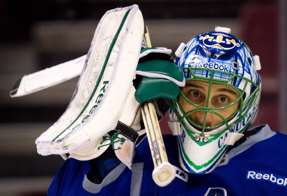 Photo -   Vancouver Canucks' goalie Roberto Luongo adjusts his mask during hockey practice in Vancouver, British Columbia on Tuesday April 10, 2012. The Vancouver Canucks and Los Angeles Kings are scheduled to play game 1 of an NHL Western Conference quarterfinal series Wednesday. (AP Photo/The Canadian Press, Darryl Dyck)