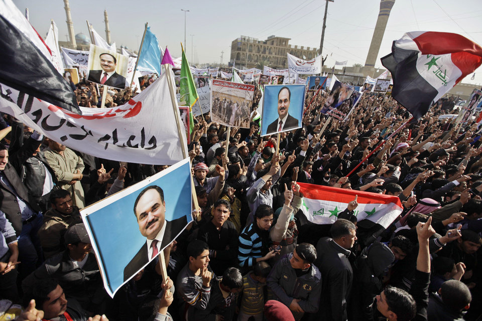 Protesters chant slogans against the Iraq\'s Shiite-led government as they wave national flags and hold posters of Sunni Finance Minister Rafia al-Issawi during a demonstration in Fallujah, 40 miles (65 kilometers) west of Baghdad, Iraq, Sunday, Dec. 23, 2012. Thousands of protesters have demonstrated in Iraq\'s western Sunni heartland following the arrest of bodyguards assigned to the finance minister, who draws support from the area. (AP Photo/ Khalid Mohammed)