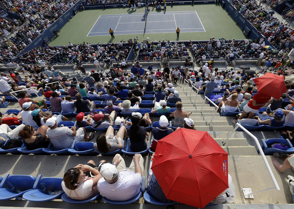 Photo - Spectator takes cover under an umbrella during the fourth round match between Eugenie Bouchard, of Canada, and Ekaterina Makarova, of Russia, in the 2014 U.S. Open tennis tournament Monday, Sept. 1, 2014, in New York. (AP Photo/Darron Cummings)