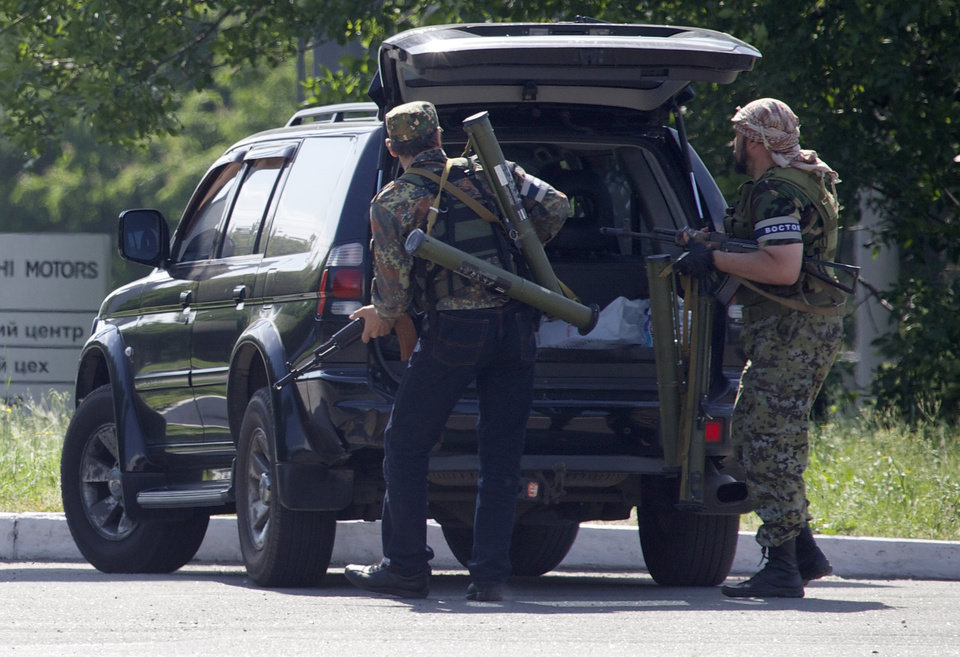 Photo - Pro-Russian insurgents arrive with weapons, near the airport outside Donetsk, Ukraine, Monday, May 26, 2014. Ukraine's military launched airstrikes Monday against the separatists who had taken over the airport in the eastern city of Donetsk, suggesting that fighting in the east is far from over. (AP Photo/Ivan Sekretarev)