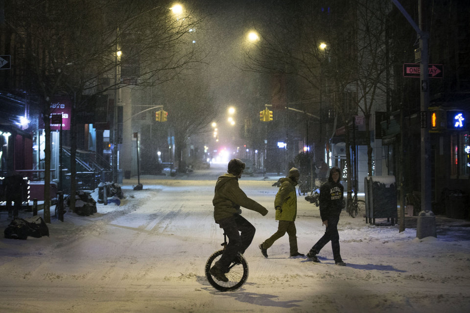 Photo - A unicyclist crosses the street during a snow storm in the SoHo neighborhood of Manhattan, Thursday, Jan. 2, 2014, in New York. The storm is expected to bring snow, stiff winds and punishing cold into the Northeast. (AP Photo/John Minchillo)